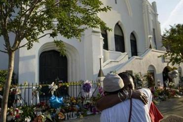 Cynthia Wright-Murphy (left) hugs her sister Carolyn Wright-Porcher outside the Emanuel church.